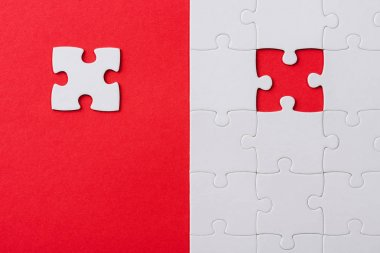 top view of unfinished white puzzles near separate piece isolated on red