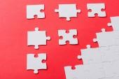 bílá spojené a oddělené puzzle kousky izolované na červené