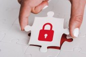 close up of woman holding white jigsaw with red padlock near connected puzzle pieces