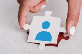 close up of woman holding white jigsaw with blue human icon near connected puzzle pieces