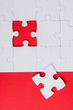 top view of incomplete white puzzles near separate piece isolated on red