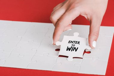 cropped of woman holding jigsaw with enter to win lettering near connected white puzzle pieces on red