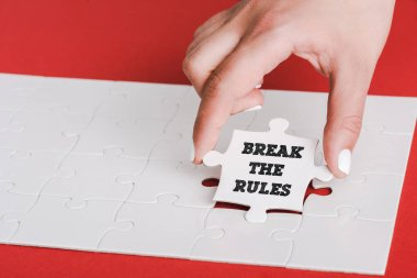 cropped of woman holding jigsaw with break the rules lettering near connected white puzzle pieces on red