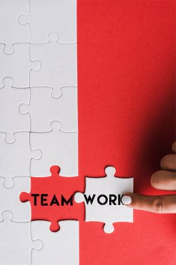 Top view of woman pointing with finger at jigsaw near connected puzzle pieces with teamwork lettering on red stock vector