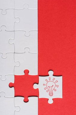 top view of incomplete jigsaw near white puzzle piece with light bulb isolated on red
