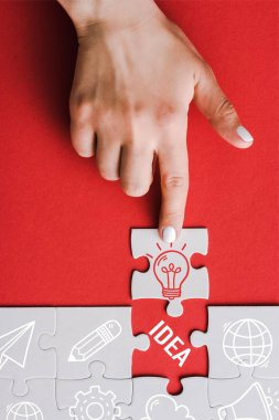 top view of woman pointing with finger at jigsaw with light bulb near connected white puzzle pieces and idea lettering on red