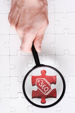 Top view of man holding magnifying glass near jigsaw with seo lettering near white connected puzzle pieces stock vector