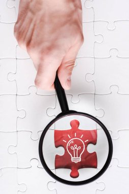 top view of man holding magnifying glass near jigsaw with light bulb near white connected puzzle pieces