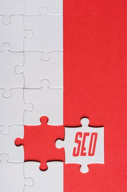 top view of incomplete jigsaw near white puzzle piece with seo lettering isolated on red