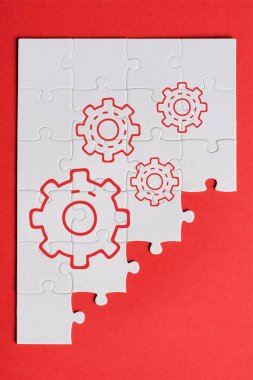 top view of white connected puzzle pieces with gears settings isolated on red