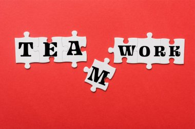 top view of white connected jigsaw near puzzle piece with teamwork lettering isolated on red