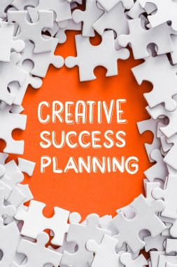 top view of frame of white jigsaw puzzle pieces around creative, success and planning lettering on orange