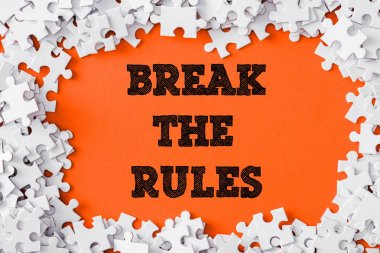 top view of frame of white jigsaw puzzle pieces around break the rules lettering on orange