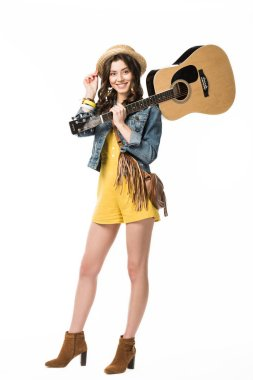 full length view of smiling hippie girl holding acoustic guitar isolated on white