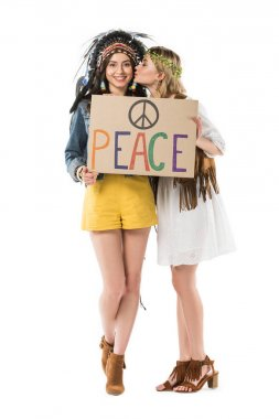 full length view of two bisexual hippie girls in indian headdress and wreath holding placard with inscription and kissing isolated on white