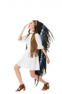 full length view of hippie girl in indian headdress dancing isolated on white