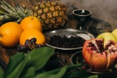 hookah, tobacco, apples, grapes, oranges, garnet and pineapple on wooden surface