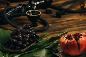 garnet, grapes, green leaves and hookah on wooden surface