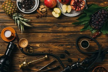 top view of tobacco, hookah, coals, cinnamon, cup of milk and exotic fruits on wooden surface