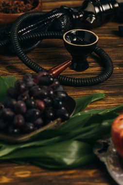 selective focus of grapes and hookah on wooden surface