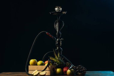 fresh tasty fruits and hookah on wooden surface isolated on black