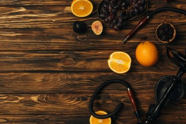 top view of fresh exotic fruits and hookah on wooden surface