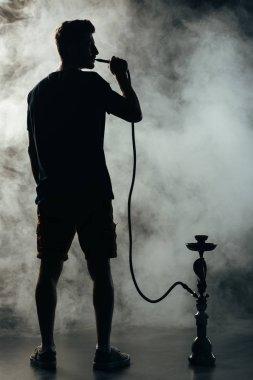 full length view of silhouette smoking hookah in darkness