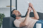 mosolygó ember fejhallgató feküdt a kanapén és a smartphone