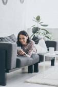hübsche Frau liegt auf Sofa, benutzt Smartphone und hört Musik über Kopfhörer
