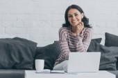 fröhliche junge Frau lächelt in die Kamera, während sie am Tisch neben dem Laptop sitzt