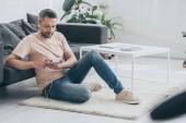 pohledný muž, který sedí doma na podlaze, používá smartphone a poslouchá hudbu v sluchátka