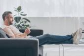 pohledný muž v sluchátek, který používá smartphone, zatímco sedí na pohovce s nohama na stole