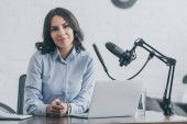 Photo beautiful radio host looking at camera while sitting at workplace near microphone and laptop