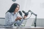 Photo pretty radio host speaking in microphone and gesturing in broadcasting studio