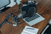 Photo laptop and notebook on wooden table near microphone in broadcasting studio