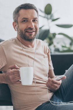 handsome man looking at camera while listening music in earphones and holding coffee cup