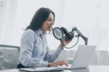 pretty radio host using laptop while speaking in microphone at workplace in broadcasting studio
