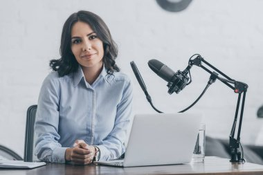 beautiful radio host looking at camera while sitting at workplace near microphone and laptop