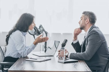 pretty radio host interviewing businessman in broadcasting studio