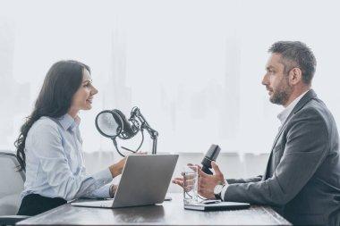 handsome businessman talking to pretty radio host during interview in radio studio