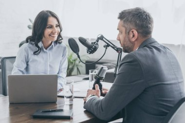 attractive smiling radio host interviewing businessman in radio studio