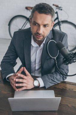 thoughtful radio host speaking in microphone in broadcasting studio