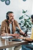 Photo cheerful radio hosts in headphones recording podcast in broadcasting studio