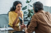 Photo beautiful attentive radio host looking at colleague while sitting at workplace in radio studio