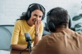 Photo selective focus of cheerful radio host laughing while recording podcast with colleague