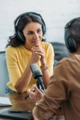 Photo selective focus of attentive radio host in headphones looking at colleague while sitting near microphone in broadcasting studio