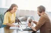 zwei seriöse Radiomoderatoren unterhalten sich am Arbeitsplatz im Hörfunkstudio
