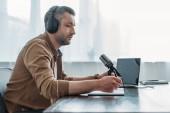 Photo serious radio host in headphones sitting near microphone in broadcasting studio