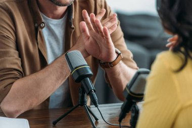 Cropped view of radio host showing no sign while recording podcast with colleague stock vector