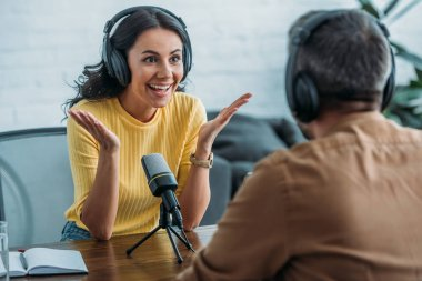 selective focus of excited radio host gesturing while looking at colleague in radio studio